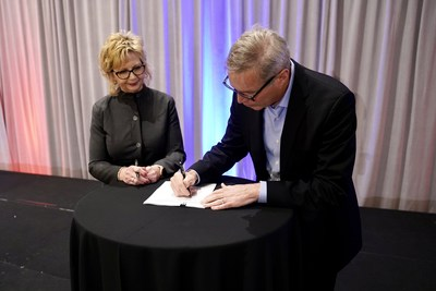 American Trucking Associations President and CEO Chris Spear signs a five-year contract extension with the association as ATA Chair Sherri Garner Brumbaugh, president and CEO of Garner Transportation Group, looks on.