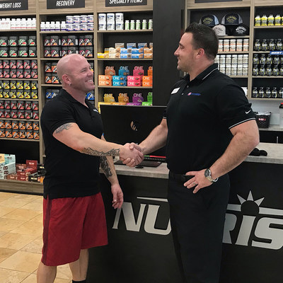 Jake Halvig (left), NUTRISHOP® franchisee of the Roseville, CA location and the flagship 24 Hour Fitness®/Nutrishop Pro Shop shakes hands with Tony Cigliutti (right), General Manager, 24 Hour Fitness Sacramento Downtown club.
